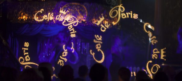 Two performers on stage at Café de Paris spin LED light wands. They display graphics of the Café de Paris logo in the air.