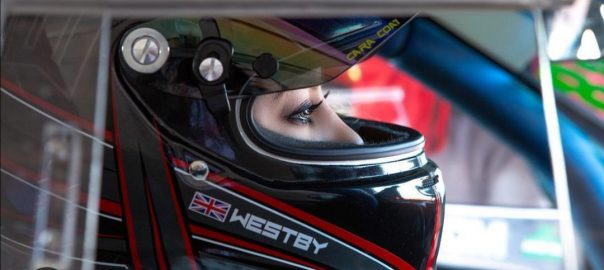 A woman wearing a driving helmet sits in a sports car, she looks out of the visor and the photo is taken from a profile angle.